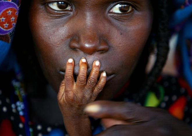 Hình ảnh bé Glassa Galisou, 1 tuổi, mắc chứng suy dinh dưỡng đang đặt bàn tay gầy gò lên miệng của mẹ em tại khu vực cung cấp thức ăn khẩn cấp ở thị trấn Tahoua, phía tây bắc Niger.