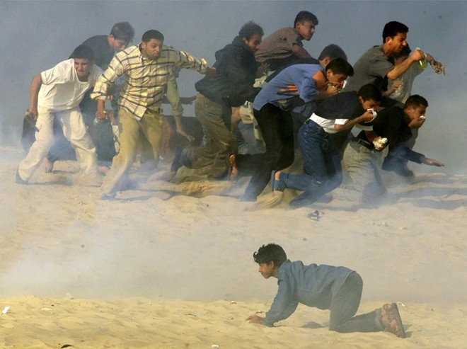 Người dân Palestine cố chạy thoát khỏi loạt hơi cay do các binh sĩ Israel bắn trong một cuộc đụng độ tại thị trấn Khan Younis, phía nam của dài Gaza.