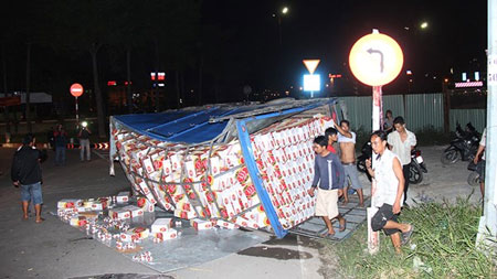 Xe tải chở bia lật, dân giúp tài xế gom hàng 2