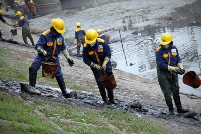 Các công nhân chuyền tay nhau các xô đựng bùn đất, rác thải lên bờ.