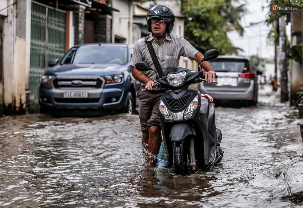 Chùm ảnh: Khách Tây trên Phố nhà giàu Sài Gòn nhăn mặt vì lội nước đẩy bộ xe chết máy trong ngày triều cường đạt đỉnh - Ảnh 4.