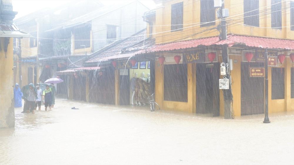 Ảnh: Người dân Hội An hối hả dọn đồ chạy lũ, du khách thích thú lội nước chụp ảnh giữa trời mưa - Ảnh 2.