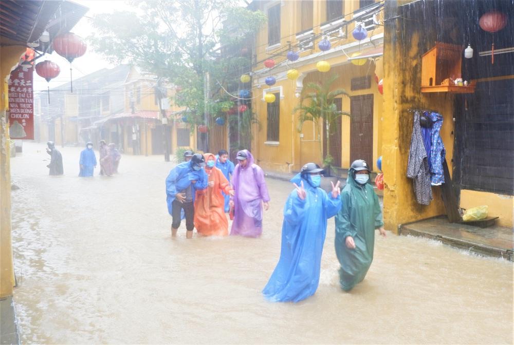 Ảnh: Người dân Hội An hối hả dọn đồ chạy lũ, du khách thích thú lội nước chụp ảnh giữa trời mưa - Ảnh 7.