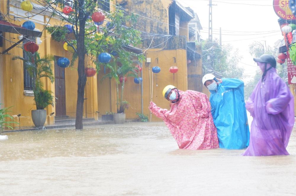 Ảnh: Người dân Hội An hối hả dọn đồ chạy lũ, du khách thích thú lội nước chụp ảnh giữa trời mưa - Ảnh 9.