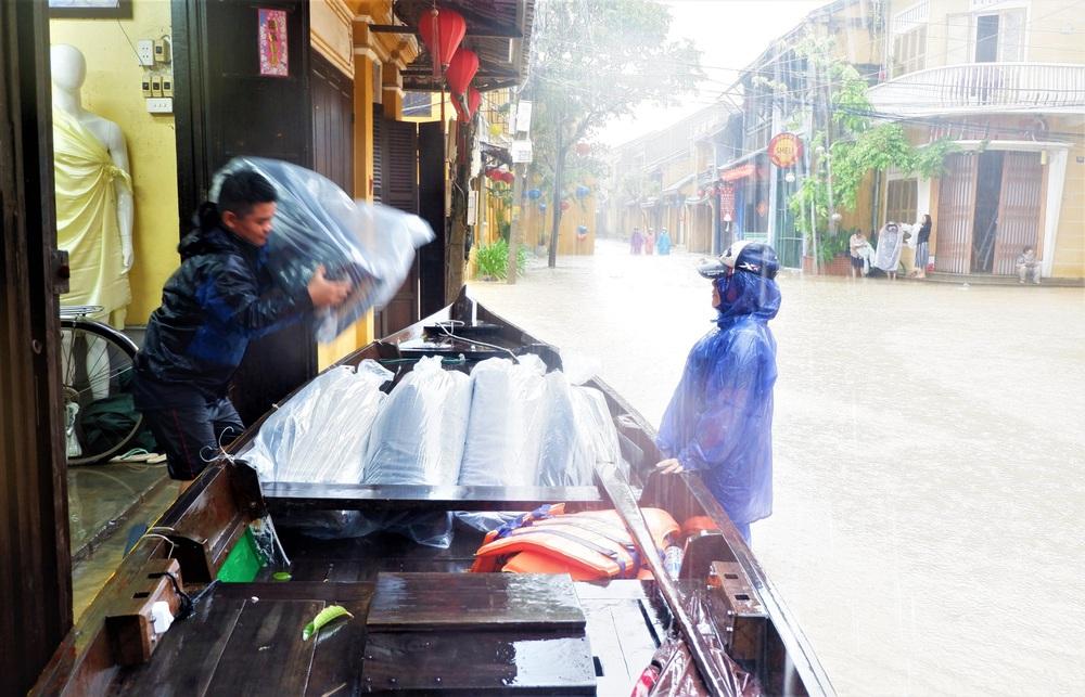 Ảnh: Người dân Hội An hối hả dọn đồ chạy lũ, du khách thích thú lội nước chụp ảnh giữa trời mưa - Ảnh 4.