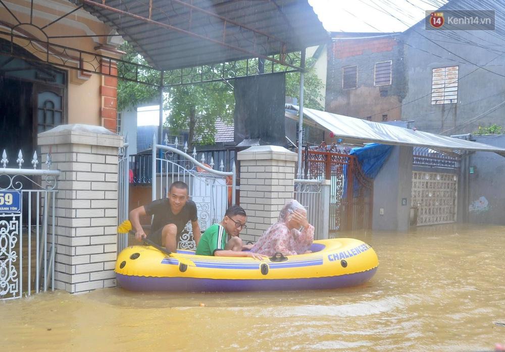 Ảnh: Huế ngập sâu trong biển nước, người dân phải chèo thuyền, lội nước đi mua thực phẩm, sạc điện thoại - Ảnh 6.