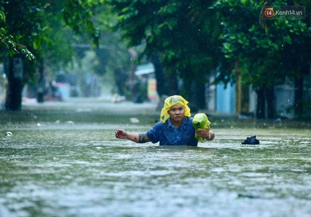 Ảnh: Huế ngập sâu trong biển nước, người dân phải chèo thuyền, lội nước đi mua thực phẩm, sạc điện thoại - Ảnh 2.