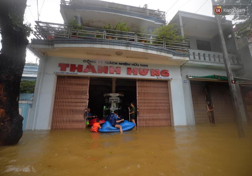 Ảnh: Huế ngập sâu trong biển nước, người dân phải chèo thuyền, lội nước đi mua thực phẩm, sạc điện thoại - Ảnh 17.