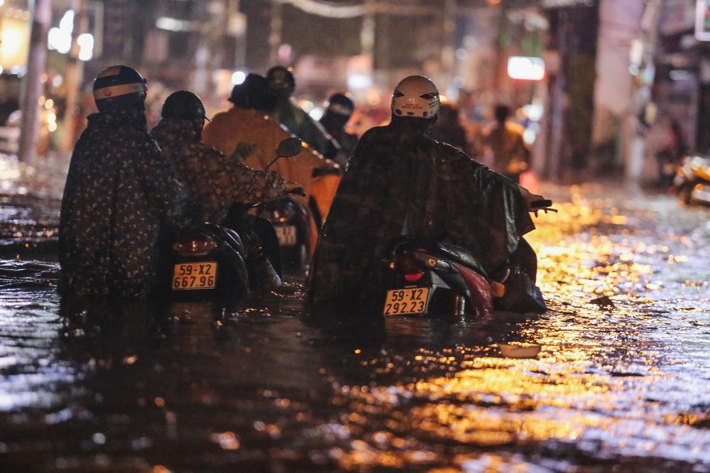 Người Sài Gòn vật lộn với đường ngập lút bánh xe, nước chảy cuồn cuộn như thác trong đêm mưa lớn - Ảnh 6.