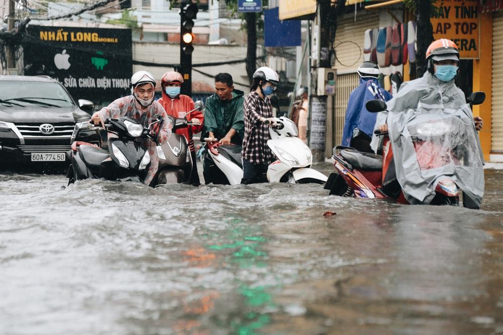 Ảnh: Đường Sài Gòn ngập lút bánh xe khi mưa lớn, người dân té ngã sõng soài - Ảnh 10.