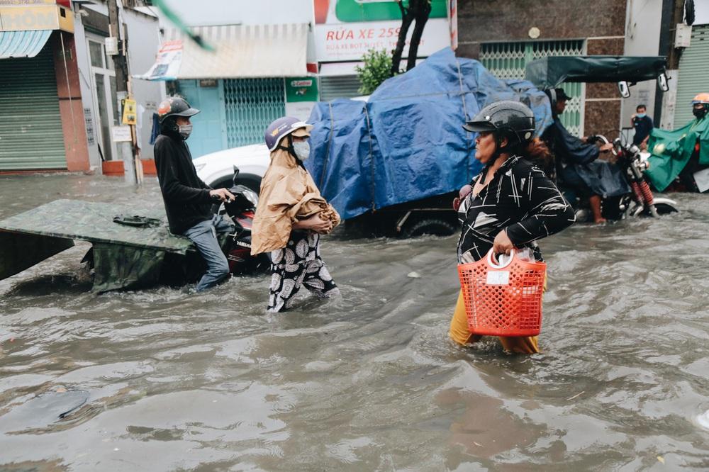 Ảnh: Đường Sài Gòn ngập lút bánh xe khi mưa lớn, người dân té ngã sõng soài - Ảnh 18.