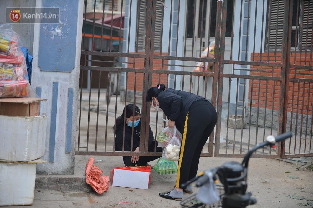 Ảnh: Người dân Đông Anh trèo cổng, mang gà, rau tiếp tế cho người thân trong khu cách ly - Ảnh 2.