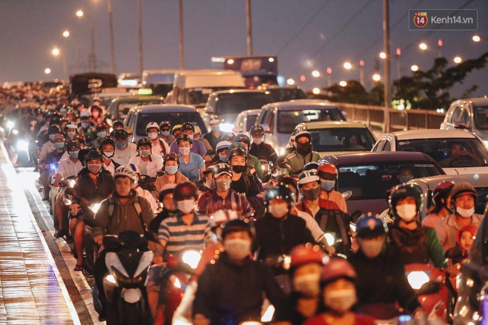 Cửa ngõ kẹt xe nghiêm trọng, hành khách kéo vali đi bộ đến bến xe Miền Đông về quê ăn Tết - Ảnh 2.