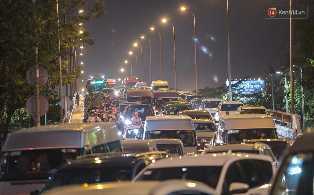Cửa ngõ kẹt xe nghiêm trọng, hành khách kéo vali đi bộ đến bến xe Miền Đông về quê ăn Tết - Ảnh 1.