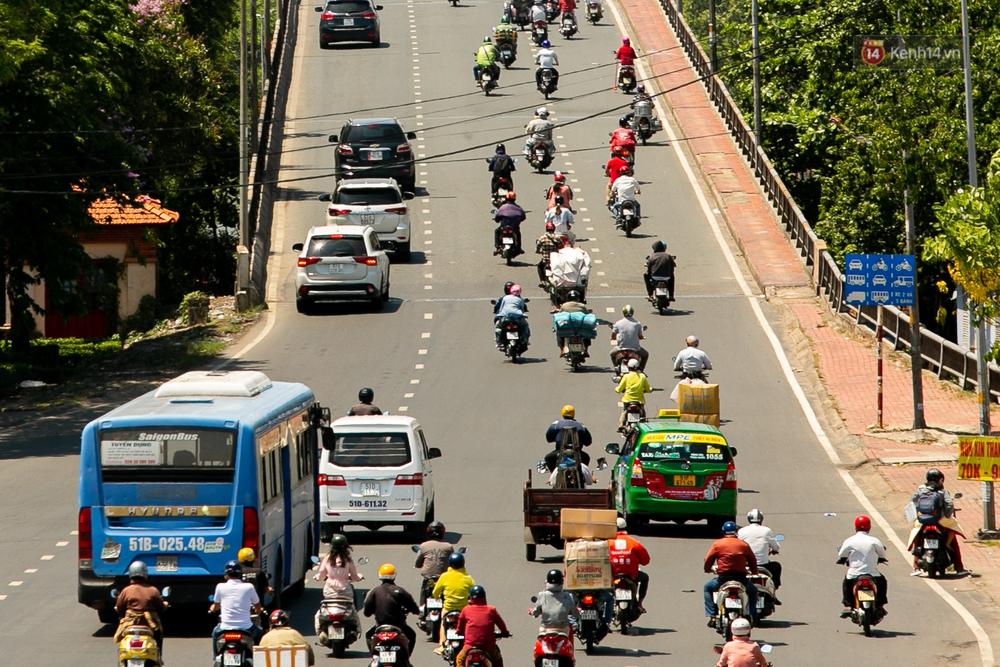 Chùm ảnh: Công nhân vật lộn với cái nóng hầm hập ở Sài Gòn, người đi đường mặc cả áo mưa tránh nắng - Ảnh 2.