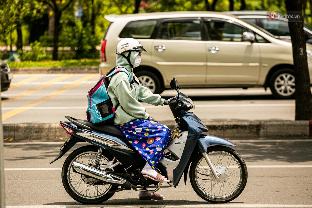 Chùm ảnh: Công nhân vật lộn với cái nóng hầm hập ở Sài Gòn, người đi đường mặc cả áo mưa tránh nắng - Ảnh 8.