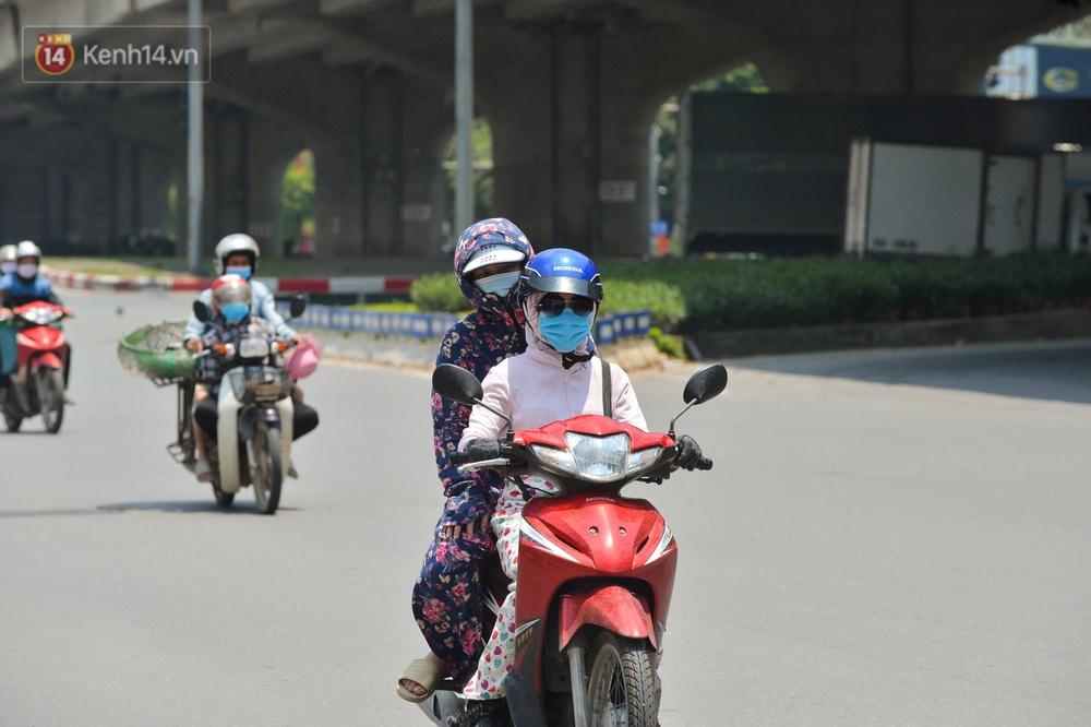 Ngày nắng nóng nhất từ đầu hè lên đến 40 độ C: Đường phố Hà Nội bốc hơi, người dân vất vả che kín mít - Ảnh 4.