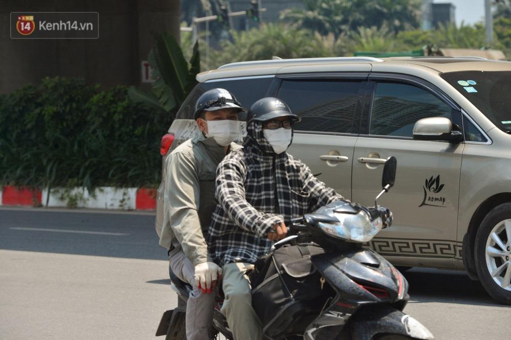 Ngày nắng nóng nhất từ đầu hè lên đến 40 độ C: Đường phố Hà Nội bốc hơi, người dân vất vả che kín mít - Ảnh 7.