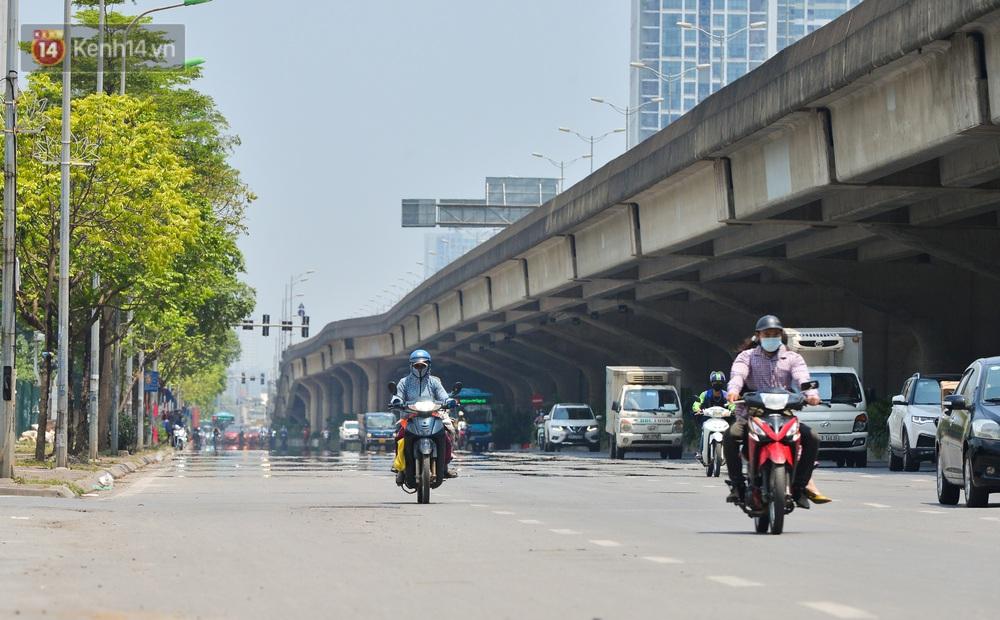 Ngày nắng nóng nhất từ đầu hè lên đến 40 độ C: Đường phố Hà Nội bốc hơi, người dân vất vả che kín mít - Ảnh 1.