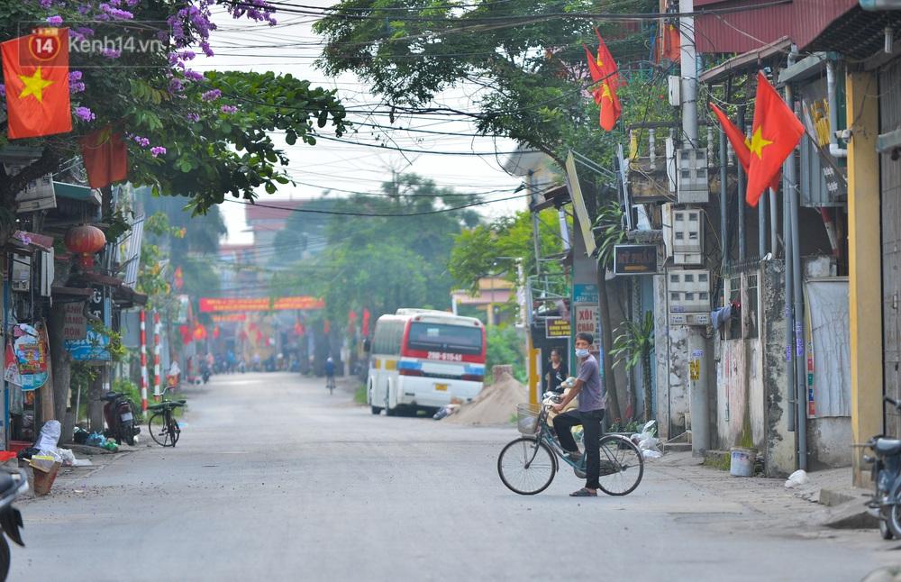 Ảnh: Người dân Thường Tín mặc áo mưa, áo bảo hộ vào khu cách ly - Ảnh 1.