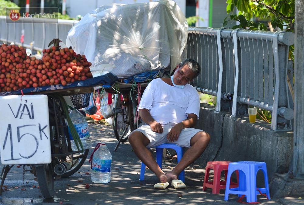 Nắng nóng đỉnh điểm lên đến gần 50 độ C tại Hà Nội: Mặt đường bốc hơi, người dân chật vật mưu sinh - Ảnh 10.