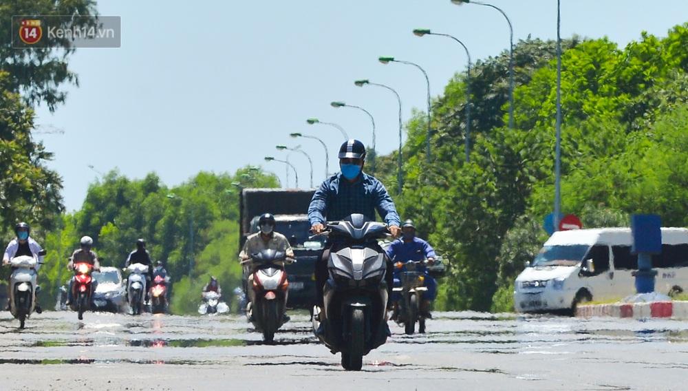Nắng nóng đỉnh điểm lên đến gần 50 độ C tại Hà Nội: Mặt đường bốc hơi, người dân chật vật mưu sinh - Ảnh 3.