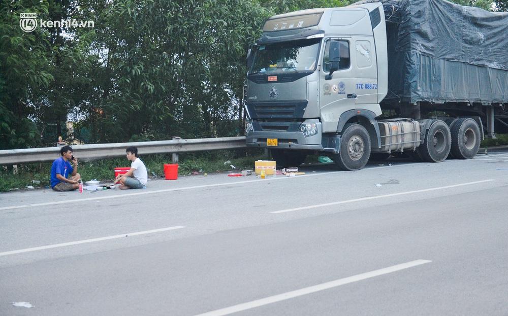 Tài xế container nấu ăn bên lề đường, chờ giấy thông hành để vào Hà Nội: Tôi bị kẹt ở đây 5 ngày rồi chưa chuyển hàng được - Ảnh 1.