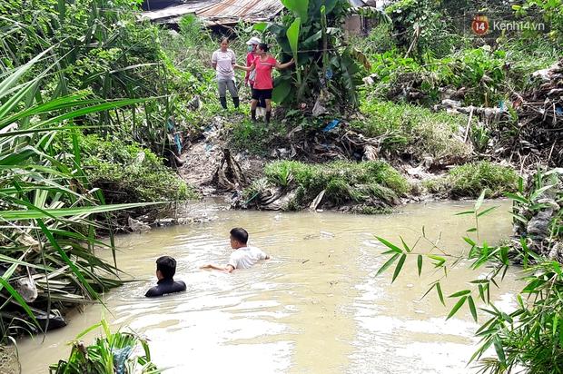 Chùm ảnh: Lội suối, lật nắp cống tìm tung tích bé trai bị nước cuốn trôi ở Bình Dương - Ảnh 2.