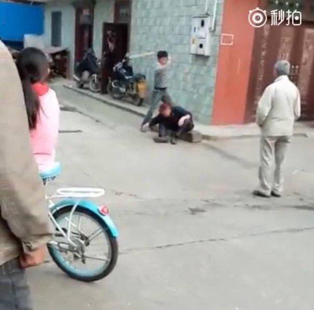 Video gây phẫn nộ: Con trai đánh bố như bổ củi giữa đường phố, người đi đường bàng quan đứng nhìn - Ảnh 2.