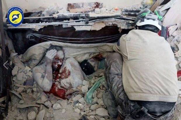 Ám ảnh bức hình người mẹ gục chết bên xác con trai bé nhỏ, tay ôm chặt đứa con mới sinh sau trận không kích - Ảnh 1.
