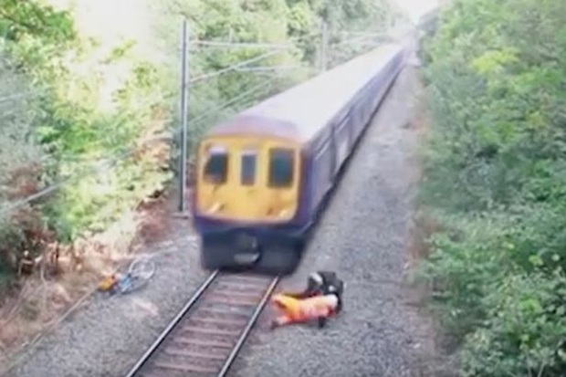 Nhân viên đường sắt dũng cảm lao mình cứu người khi đoàn tàu ầm ầm đi tới - Ảnh 1.