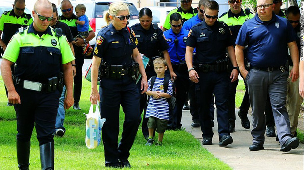 Câu chuyện buồn đằng sau bức hình em bé 4 tuổi đi khai giảng với 18 cảnh sát theo sau - Ảnh 1.
