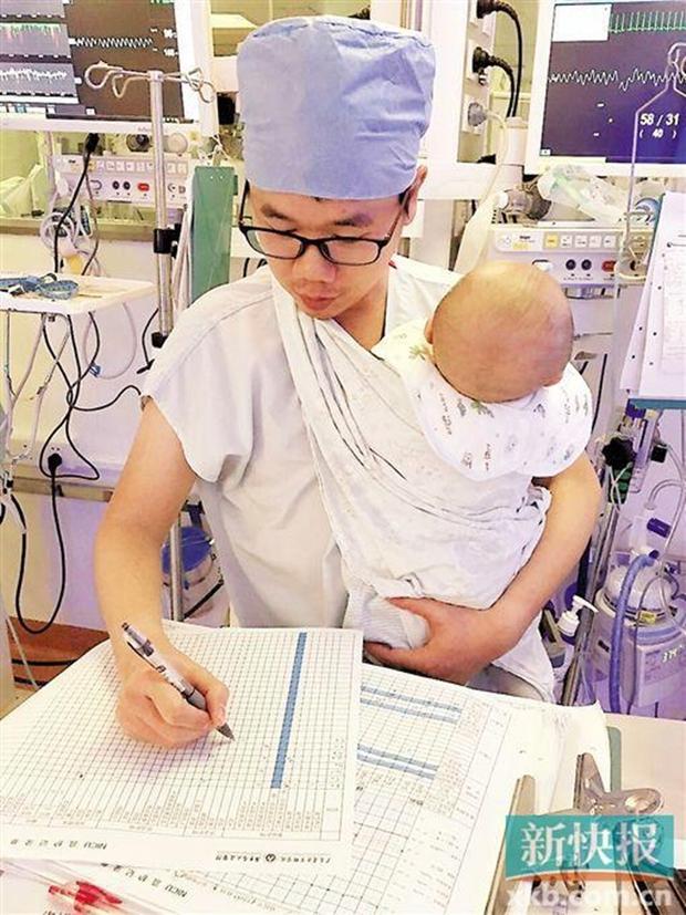Nam y tá trẻ vừa địu bệnh nhi khóc ngằn ngặt vừa say sưa làm việc gây sốt mạng xã hội - Ảnh 1.