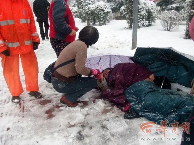 Ấm áp giữa ngày giá lạnh: Người đi đường sẵn sàng cởi áo sưởi ấm cho bà cụ ngã giữa nền tuyết - Ảnh 1.