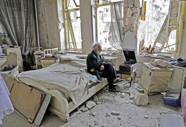 Câu chuyện cảm động phía sau bức hình người đàn ông ngồi một mình trong căn phòng bị chiến tranh tàn phá - Ảnh 1.