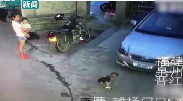 Bế con nhỏ đứng nhìn bé trai bị ô tô chèn qua người, bà mẹ trẻ không thèm biểu lộ cảm xúc - Ảnh 2.