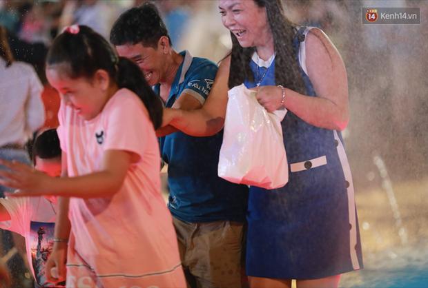 Người lớn, trẻ nhỏ nhảy vào đài phun nước ở đường hoa Nguyễn Huệ để vui đùa đêm Giao Thừa - Ảnh 3.