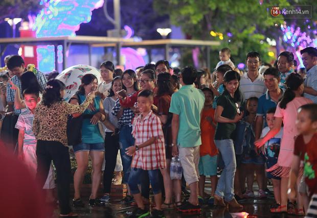 Người lớn, trẻ nhỏ nhảy vào đài phun nước ở đường hoa Nguyễn Huệ để vui đùa đêm Giao Thừa - Ảnh 1.