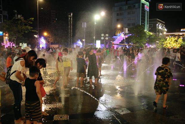 Người lớn, trẻ nhỏ nhảy vào đài phun nước ở đường hoa Nguyễn Huệ để vui đùa đêm Giao Thừa - Ảnh 2.