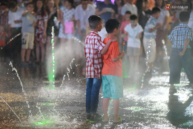 Người lớn, trẻ nhỏ nhảy vào đài phun nước ở đường hoa Nguyễn Huệ để vui đùa đêm Giao Thừa - Ảnh 6.