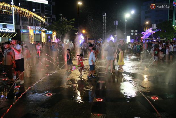 Người lớn, trẻ nhỏ nhảy vào đài phun nước ở đường hoa Nguyễn Huệ để vui đùa đêm Giao Thừa - Ảnh 5.