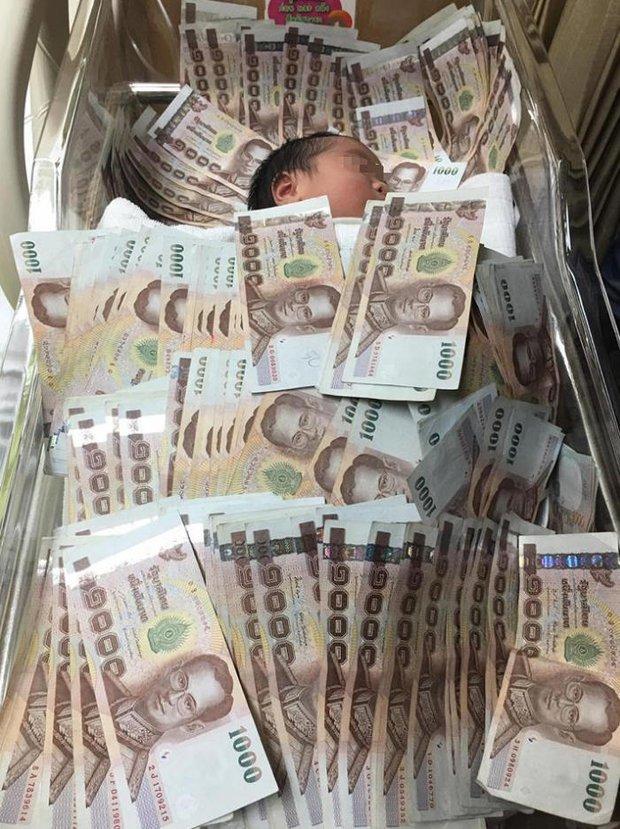 Đứa trẻ sơ sinh ngủ giữa đống tiền và nguyên do khiến nhiều người không khỏi ngao ngán - Ảnh 2.
