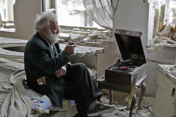 Câu chuyện cảm động phía sau bức hình người đàn ông ngồi một mình trong căn phòng bị chiến tranh tàn phá - Ảnh 9.