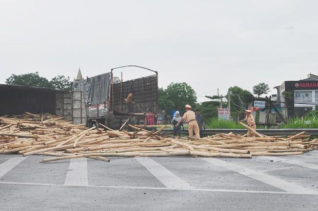 Xe chở 10 tấn gỗ lật nghiêng, chiến sỹ CSGT hỗ trợ tài xế bốc dỡ gỗ khỏi lòng đường - Ảnh 1.