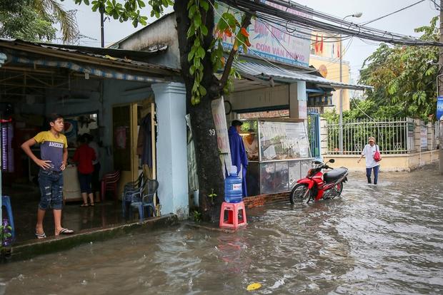 Học sinh ở Sài Gòn bì bõm lội nước sau giờ tan học do mưa lớn kéo dài từ sáng đến trưa - Ảnh 2.