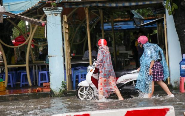 Học sinh ở Sài Gòn bì bõm lội nước sau giờ tan học do mưa lớn kéo dài từ sáng đến trưa - Ảnh 4.