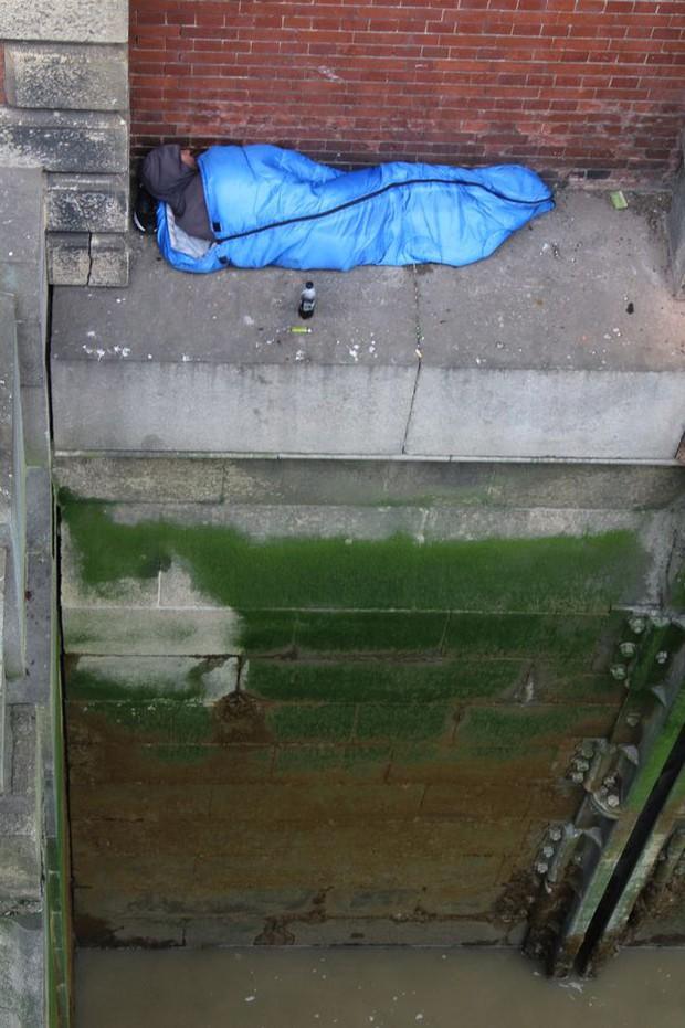 Bức ảnh người vô gia cư ngủ dưới chân cầu lột trần hiện thực khắc nghiệt tại đô thị giàu có bậc nhất thế giới - Ảnh 1.