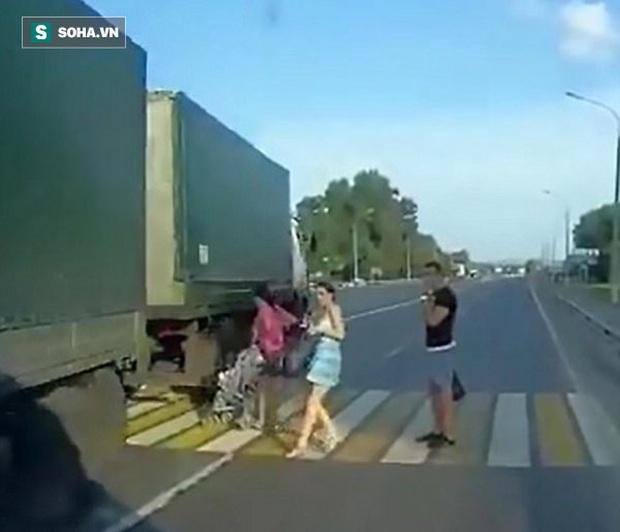Mẹ bất cẩn, xe nôi chở em bé suýt bị xe tải nuốt chửng khi sang đường - Ảnh 1.