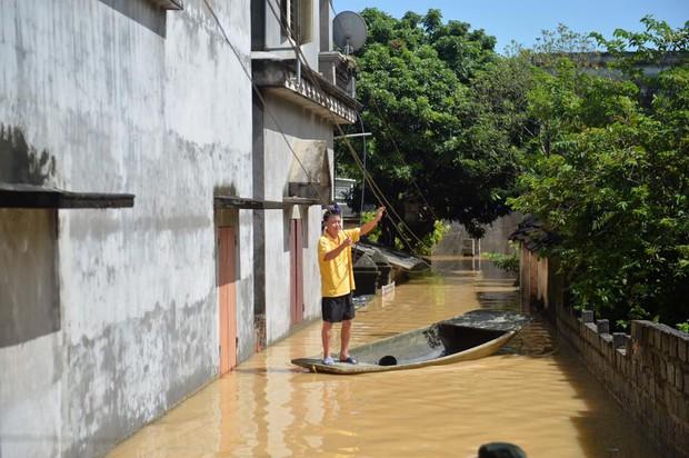 Chùm ảnh: Nhà ngập sâu đến ngang cửa, người dân Ninh Bình dùng chậu nhôm, ghế gỗ chèo thuyền đi lại trong ngõ - Ảnh 2.
