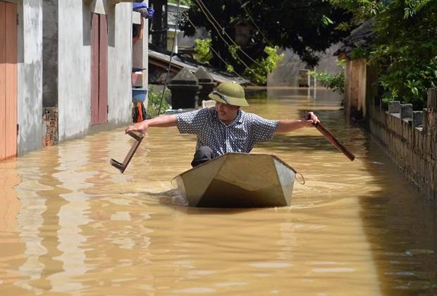 Chùm ảnh: Nhà ngập sâu đến ngang cửa, người dân Ninh Bình dùng chậu nhôm, ghế gỗ chèo thuyền đi lại trong ngõ - Ảnh 3.